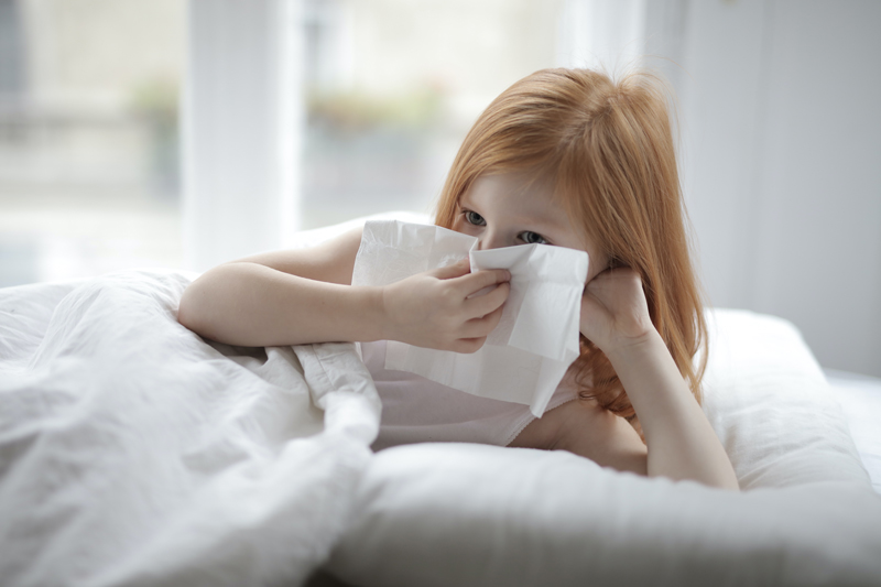 sick_little_girl_blowing_nose_with_tissue_lying_in_bed_3887616.jpg